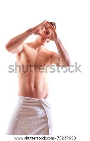 handsome  muscular man with towel making a heart with his hands - stock photo