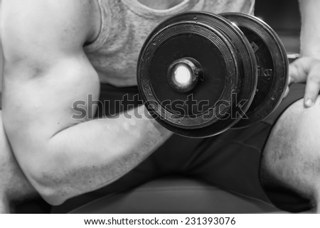 Handsome muscular man working out with dumbbells in gym.Sport, power, dumbbells, tension, exercise - the concept of a healthy lifestyle. Article about fitness and sports.