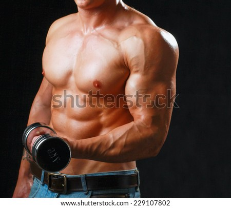 Handsome muscular man working out with dumbbells over black background. - stock photo