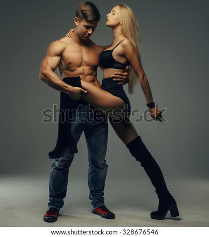 Handsome muscular shirtless guy holding long leg of his sexy blond young woman. Isolated on grey background. - stock photo