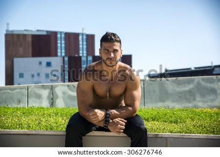 Handsome Muscular Shirtless Hunk Man Outdoor in City Setting. Showing Healthy Body While Looking At Camera - stock photo