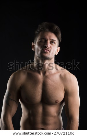 Handsome muscular, shirtless man looking up with strange expression, isolated on black - stock photo