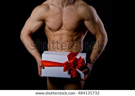 handsome muscular young man holding a present. Christmas.
