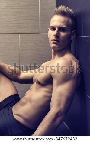 Handsome, muscular young man shirtless sitting against dark tiled wall, looking at camera