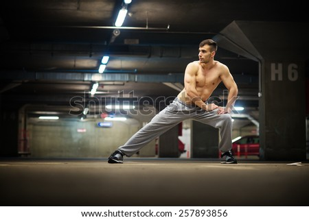 Handsome muscular young man stretching at parking garage, natural lights, dark place. - stock photo