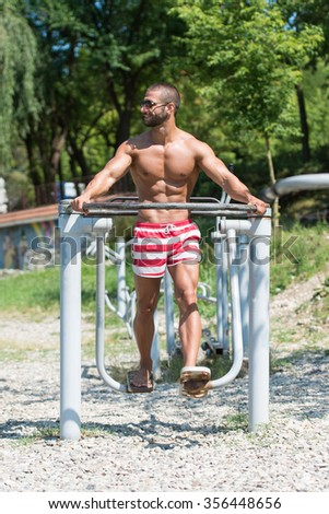 Handsome Muscular Young Man - Training On The Playground In Park