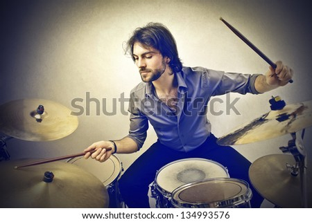 handsome musician playing drums - stock photo