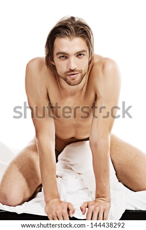 Handsome nude man lying in a bed. Isolated over white. - stock photo