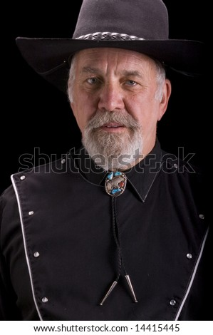 Handsome olld baby-boomer Cowboy dressed in black and looking like Buffalo Bill Cody - stock photo