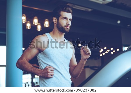 Handsome on treadmill. Low angle view of young handsome man in sportswear running on treadmill and looking away at gym - stock photo