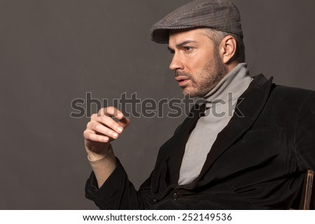 handsome pensive man in jacket and cap in vintage style - stock photo