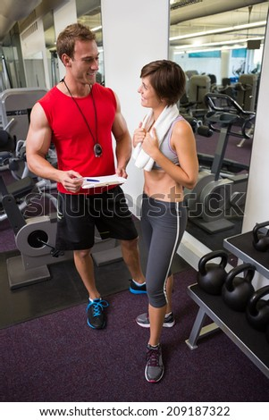 Handsome personal trainer speaking with his client at the gym