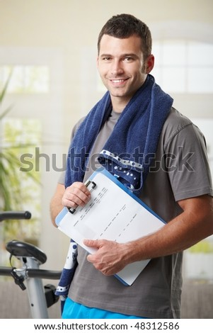 Handsome personal trainer with training plan. - stock photo