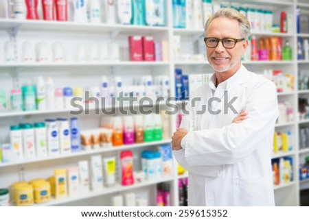 Handsome pharmacist smiling at camera at the hospital pharmacy - stock photo