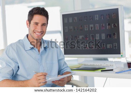 Handsome photo editor holding documents in his office - stock photo
