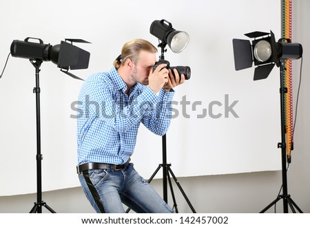 Handsome photographer with camera at working, on photo studio background - stock photo