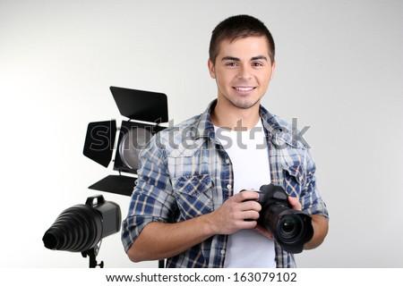 Handsome photographer with camera, on photo studio background - stock photo