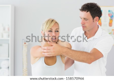 Handsome physiotherapist examining patients back in bright office - stock photo