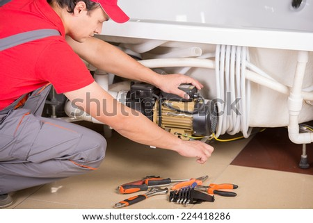 Handsome plumber is repairing bathtub. Service. - stock photo