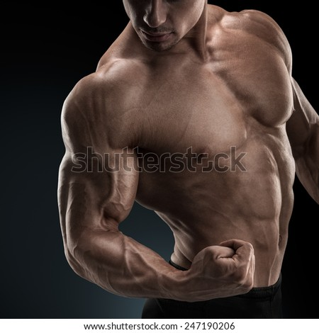 Handsome power athletic man bodybuilder demonstrates his biceps. Fitness muscular body on dark background. - stock photo