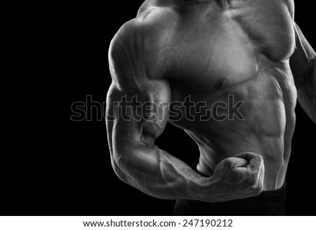 Handsome power athletic man bodybuilder demonstrates his biceps. Fitness muscular body on dark background. Black and white photo. - stock photo