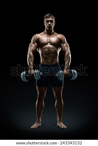 Handsome power athletic man bodybuilder doing exercises with dumbbell, confidently looking forward. Fitness muscular body on dark background. - stock photo