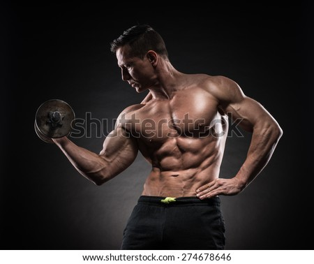 Handsome power athletic man bodybuilder doing exercises with dumbbell. Fitness muscular body on dark background. - stock photo