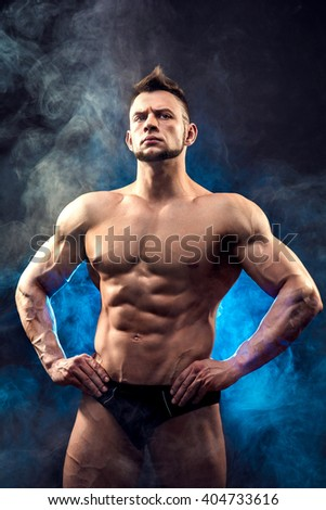 Handsome power athletic man bodybuilder. Fitness muscular body on dark smoke background. Perfect male. Awesome bodybuilder, posing.  - stock photo