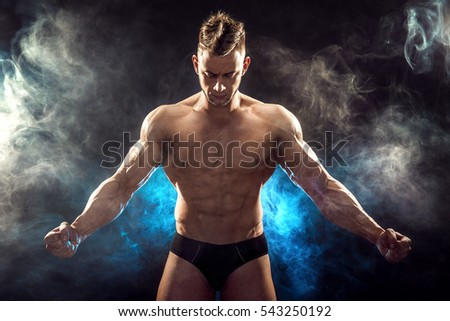 Handsome power athletic man bodybuilder. Fitness muscular body on dark smoke background. Perfect male. Awesome bodybuilder, posing.