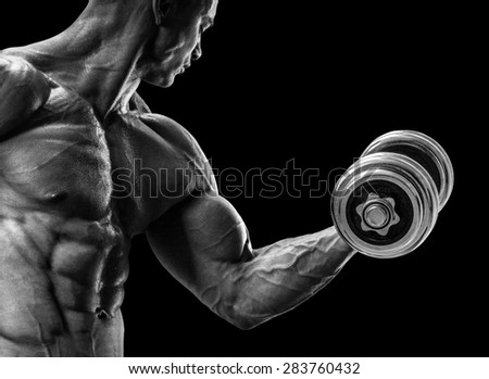Handsome power athletic man in training pumping up muscles with dumbbell. Strong bodybuilder with six pack, perfect abs, shoulders, biceps, triceps and chest. Black and white image - stock photo