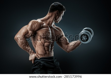 Handsome power athletic man in training pumping up muscles with dumbbell. Strong bodybuilder with six pack, perfect abs, shoulders, biceps, triceps and chest - stock photo