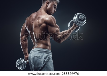 Handsome power athletic man in training pumping up muscles with dumbbells. Strong bodybuilder with six pack, perfect abs, shoulders, biceps, triceps and chest. - stock photo