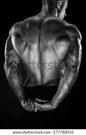 Handsome power athletic man showing his back. Strong bodybuilder with shoulders, biceps, triceps and chest. Black and white photo. - stock photo