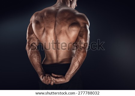 Handsome power athletic man showing his back. Strong bodybuilder with shoulders, biceps, triceps and chest - stock photo