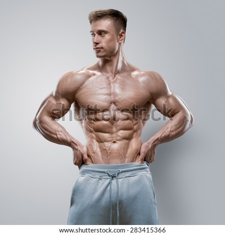 Handsome power athletic young man with great physique. Strong bodybuilder with six pack, perfect abs, shoulders, biceps, triceps and chest. Studio shot on white background - stock photo
