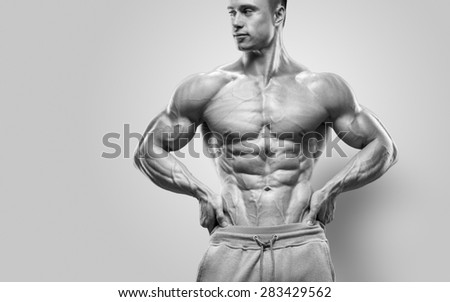 Handsome power athletic young man with great physique. Strong bodybuilder with six pack, perfect abs, shoulders, biceps, triceps and chest. Black and white image - stock photo