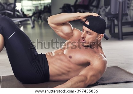 Handsome powerful athletic man performing crunches. Strong bodybuilder with perfect abs, chest and biceps. - stock photo
