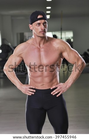 Handsome powerful athletic man posing at the gym. Strong bodybuilder with perfect abs, shoulders, arms and chest. - stock photo