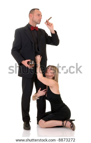 Handsome pre middle aged gigolo in formal suit with bow tie, woman at his feet, white background,  studio shot. - stock photo