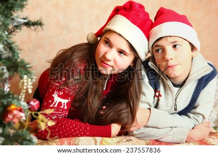 handsome preteen boy and his sister in santa hat with christmas tree