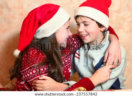 handsome preteen boy and his sister play in christmas eve - stock photo