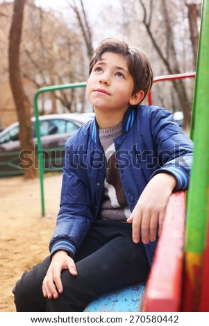 handsome preteen boy expressive thoughtfull portrait on the playground - stock photo