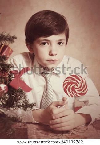 handsome preteen boy in with round candy retro old photo - stock photo