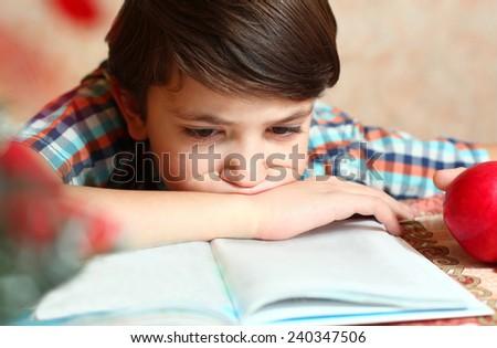 handsome preteen boy reading a book - stock photo