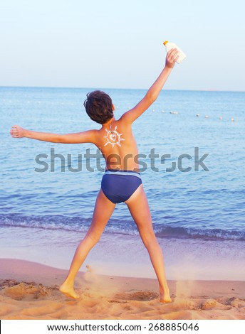 handsome preteen boy with anti sunburn cream sun drawing on his back on the sea sand beach background