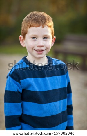 Handsome red haired boy standing outside portrait
