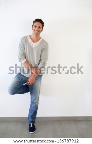 Handsome relaxed guy standing on white backgroud - stock photo