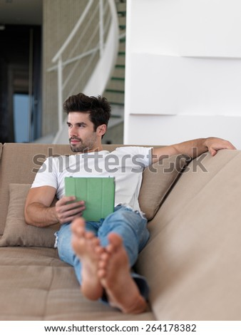 Handsome relaxed young businessman working from home on tablet computer - stock photo