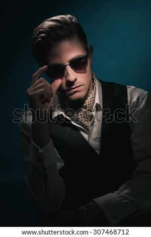 Handsome retro fashion man with vintage shades in waistcoat and scarf. Slick hair combed back. Against Dark blue background. - stock photo