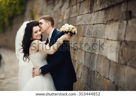 Handsome romantic groom kissing beautiful brunette bride near old wall castle - stock photo